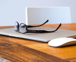 デスクの上にあるパソコンとマウスとメガネ